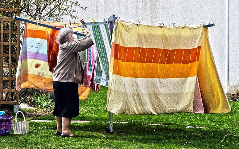Abuela colgando al sol ropa